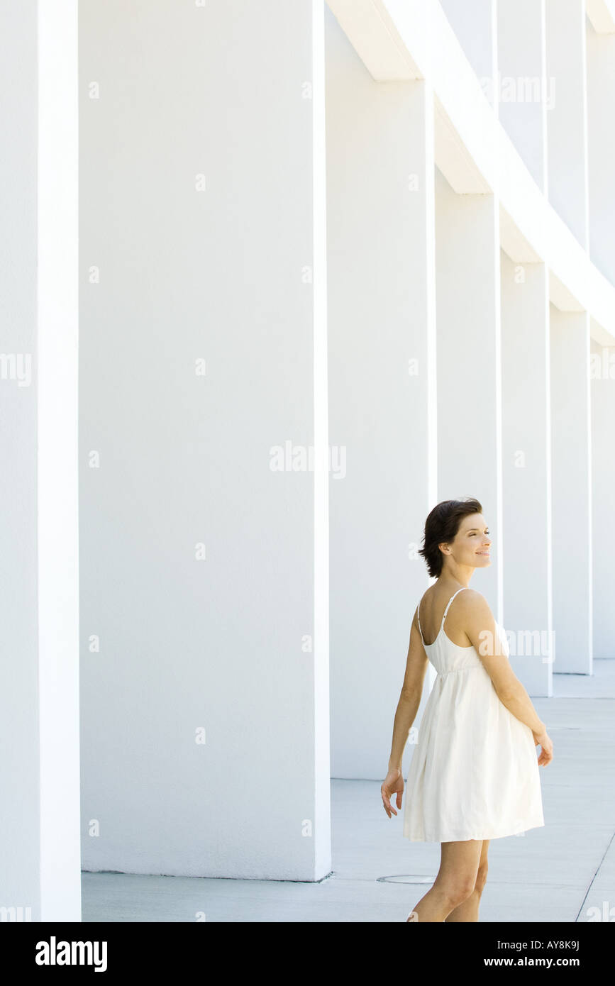 Woman in sundress walking outdoors, hair tousled by wind, smiling - Stock Image
