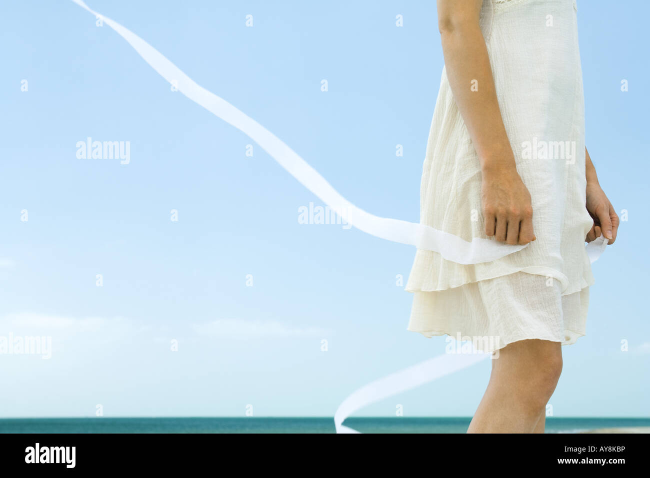 Woman in dress holding ribbon, tousled by wind, low angle view, cropped - Stock Image