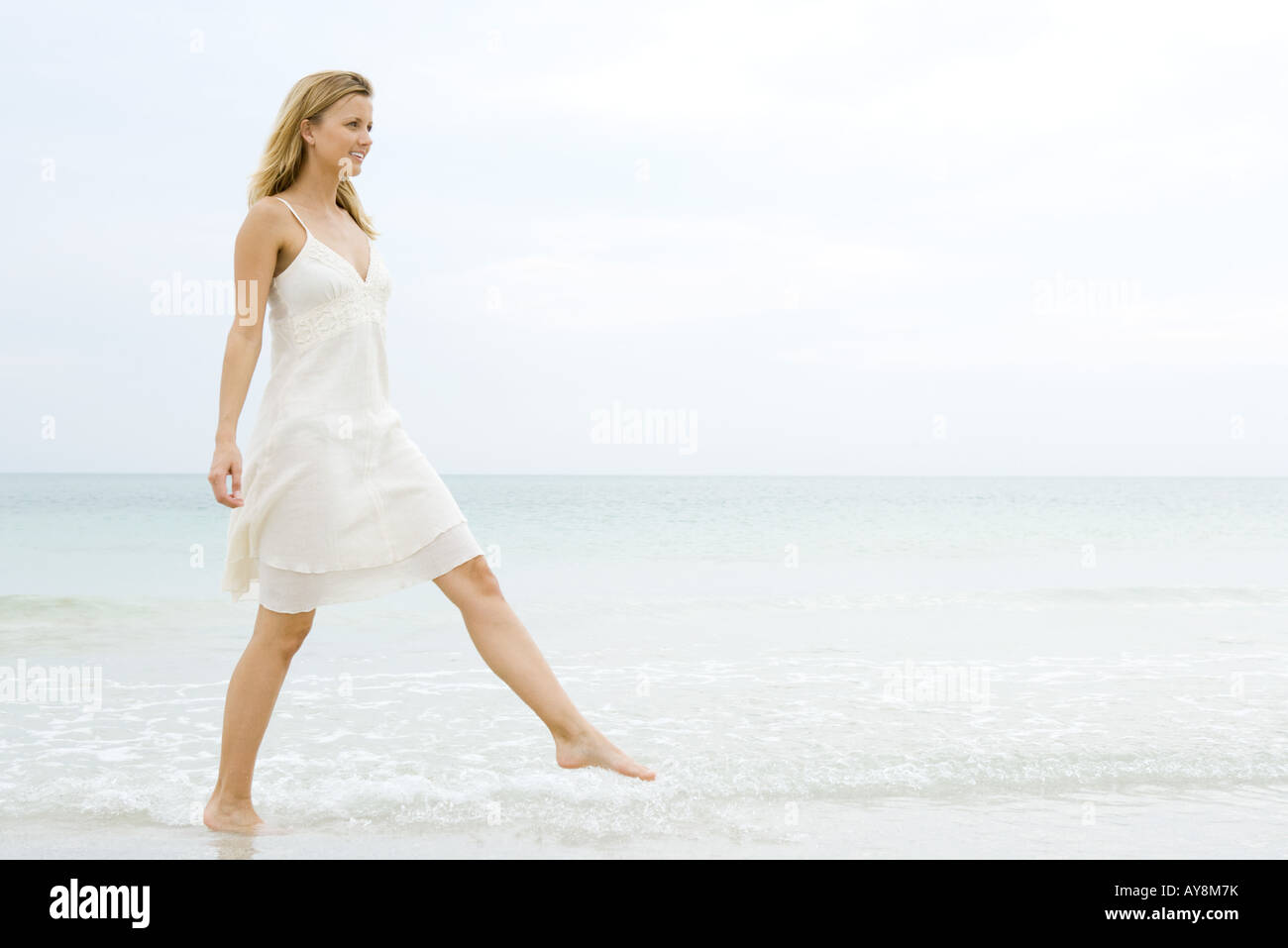 Young woman in sundress taking large step as she walks in shallow water on beach, full length - Stock Image