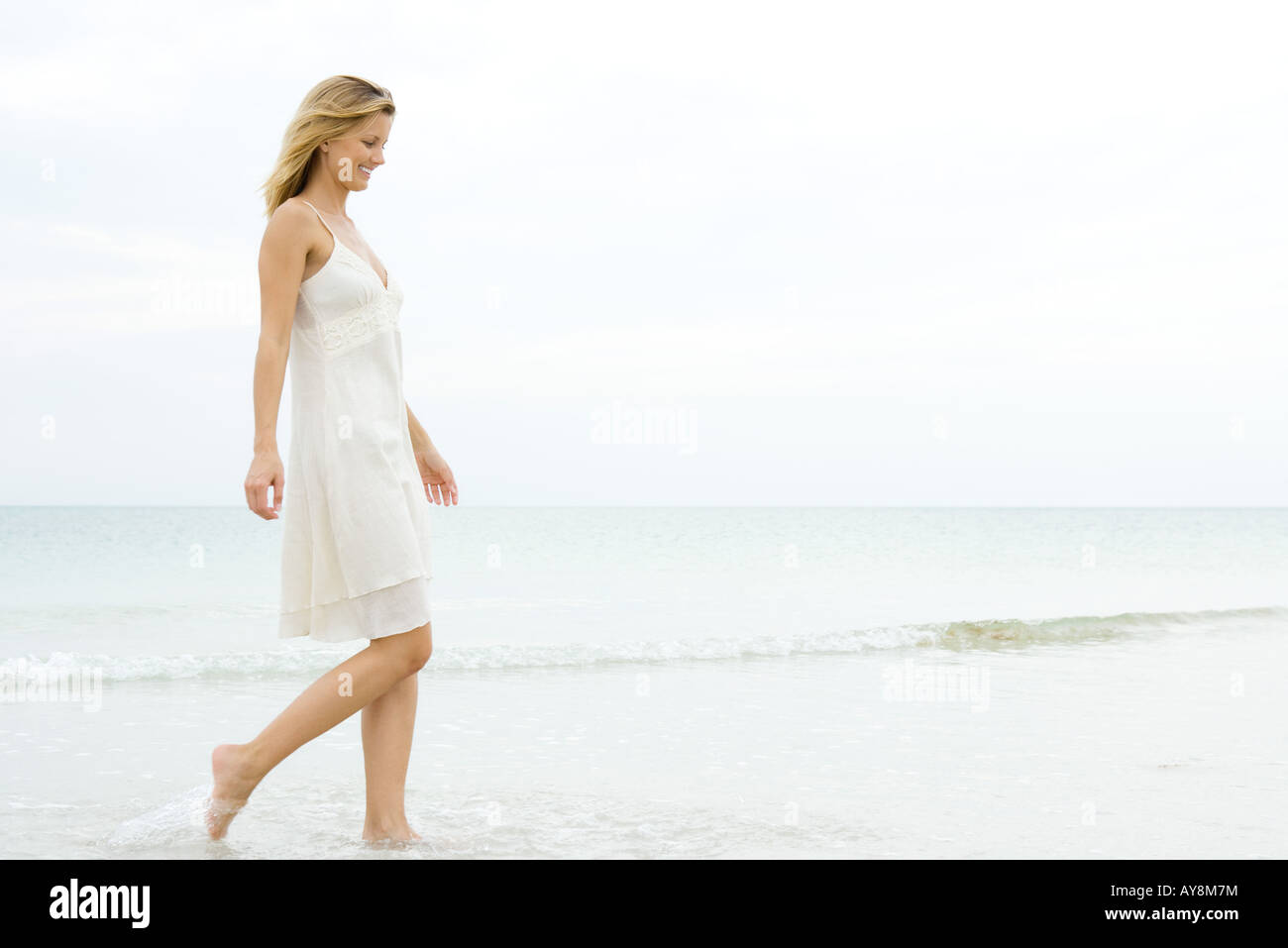 Young woman in sundress walking in surf at beach, smiling, full length - Stock Image