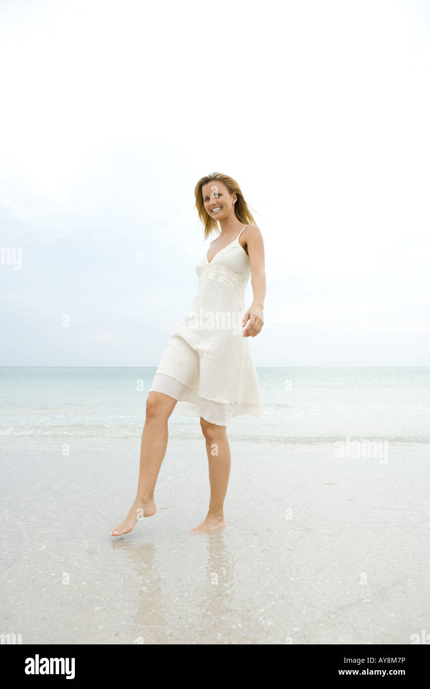 Young woman in sundress walking on wet sand at beach, smiling at camera, full length - Stock Image