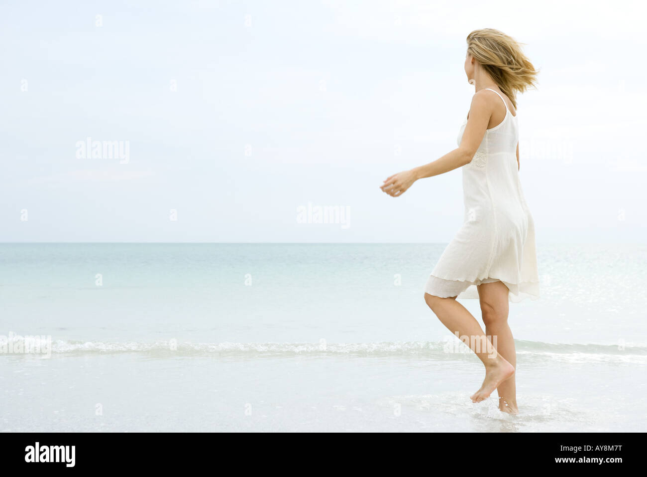 Young woman in sundress walking in shallow water at beach, looking toward horizon - Stock Image