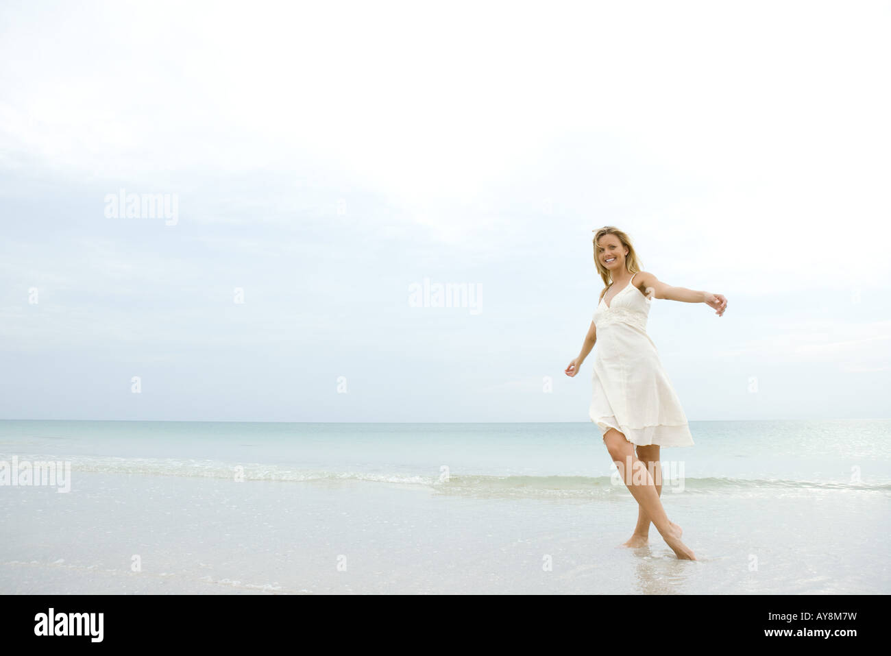 Young woman in sundress posing on beach with arms out and legs crossed, smiling at camera - Stock Image