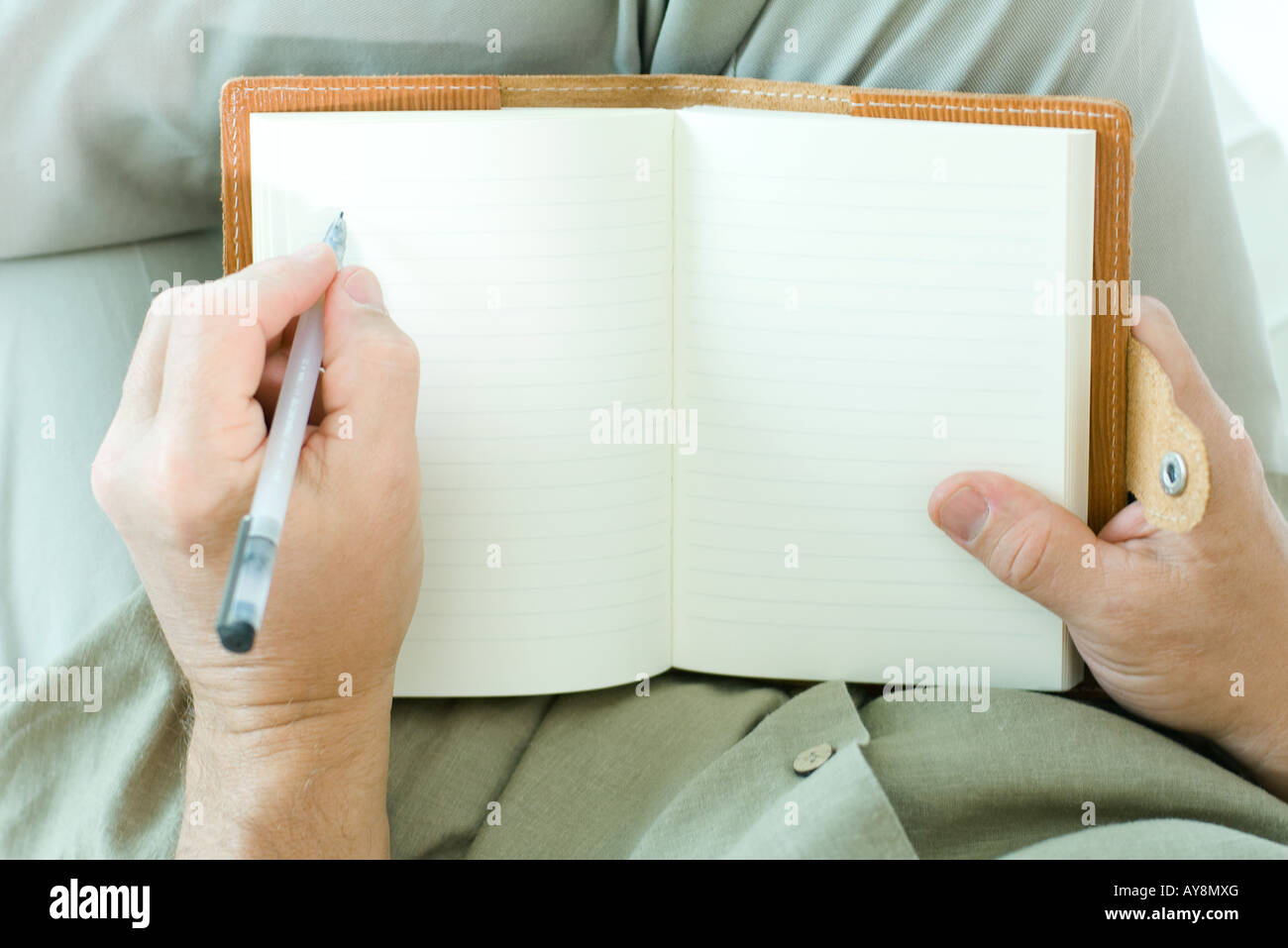 Man writing in diary, cropped view of hands - Stock Image