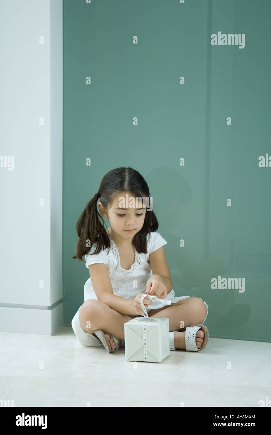 Little girl sitting on the ground, tying ribbon on gift Stock Photo