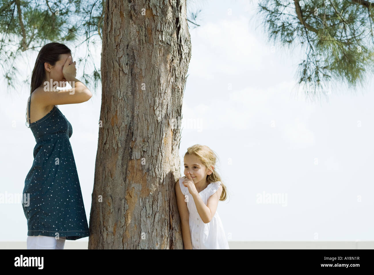 Two sisters playing hide-and-seek, one covering eyes with hands, the other peeking around tree trunk - Stock Image