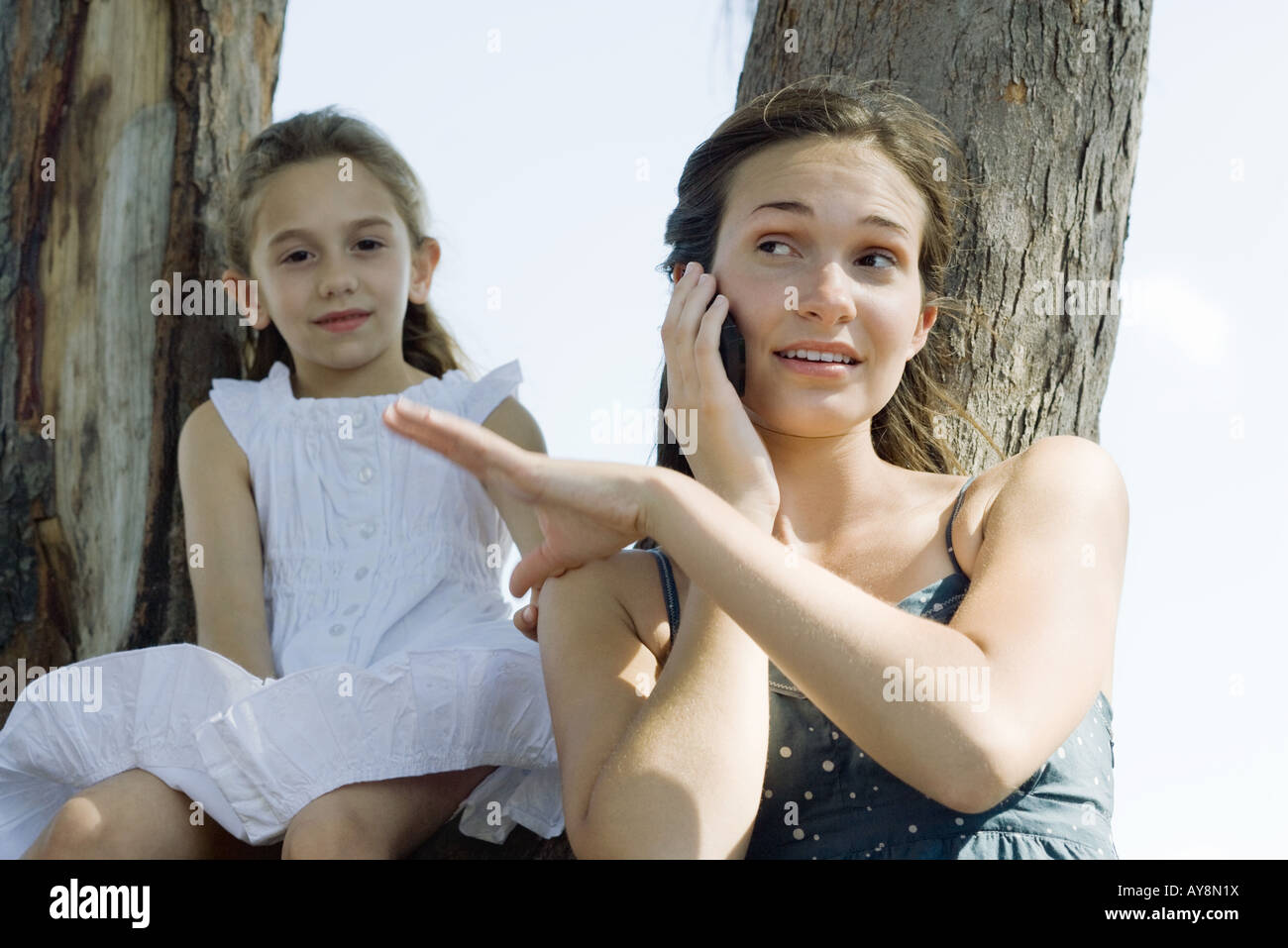 Young woman using cell phone, brushing little sister's hand off her shoulder Stock Photo