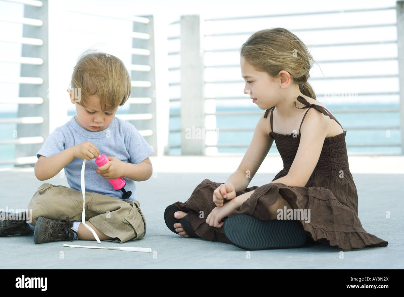 Little boy sitting on the ground inflating balloon with air pump, older sister watching Stock Photo