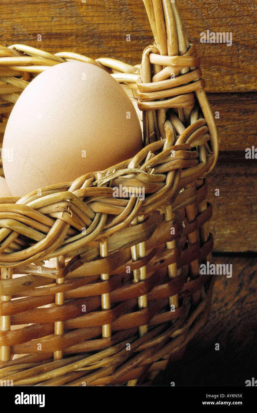 Egg in wicker basket, close-up - Stock Image
