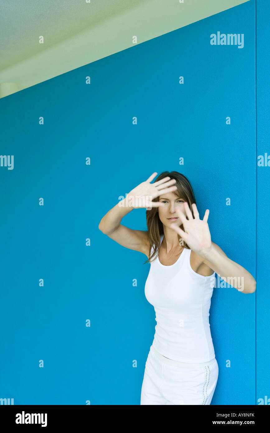 Woman leaning against wall, holding hands up in front of face, looking at camera - Stock Image