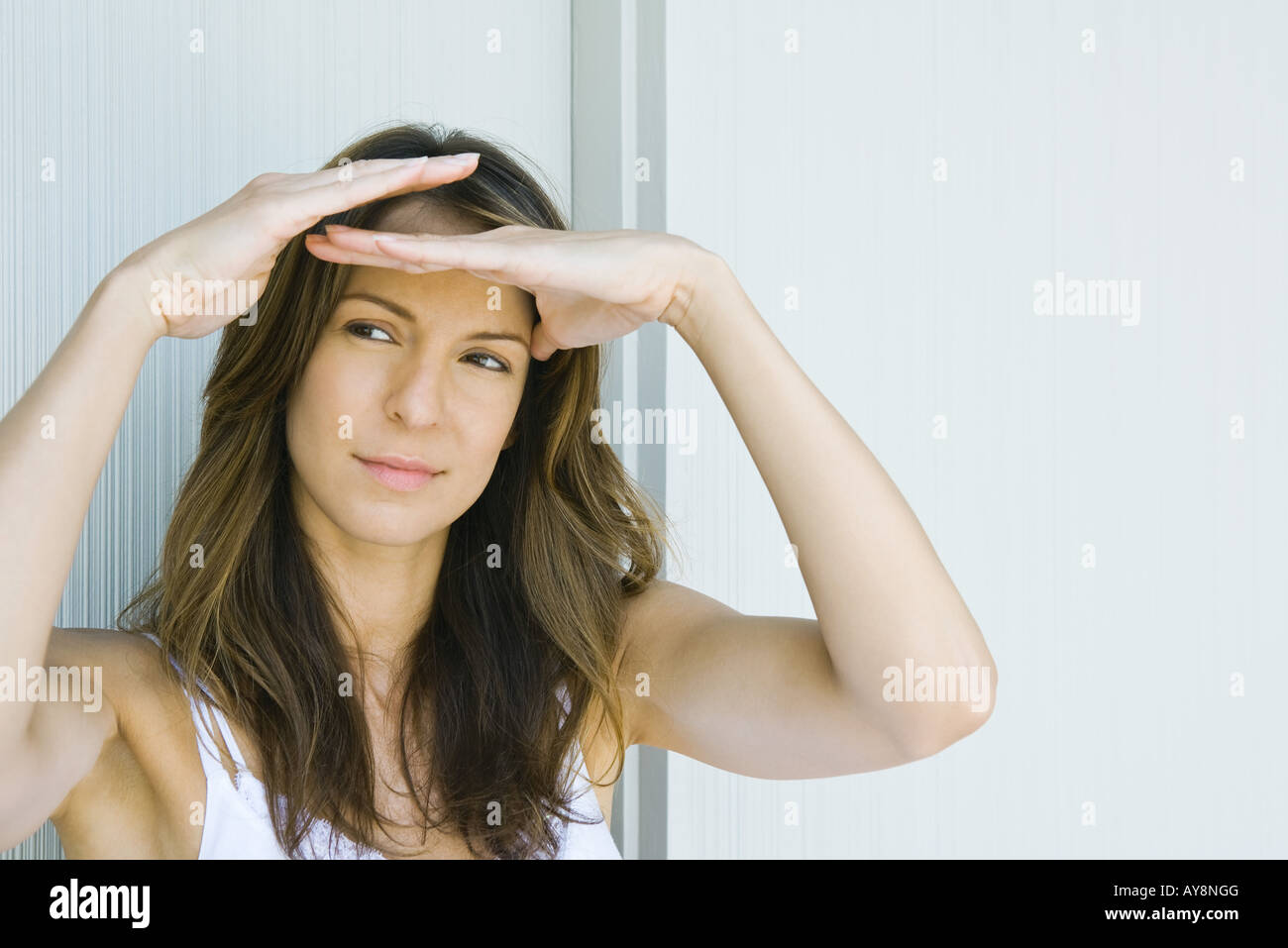 Woman shading eyes, looking away, close-up - Stock Image