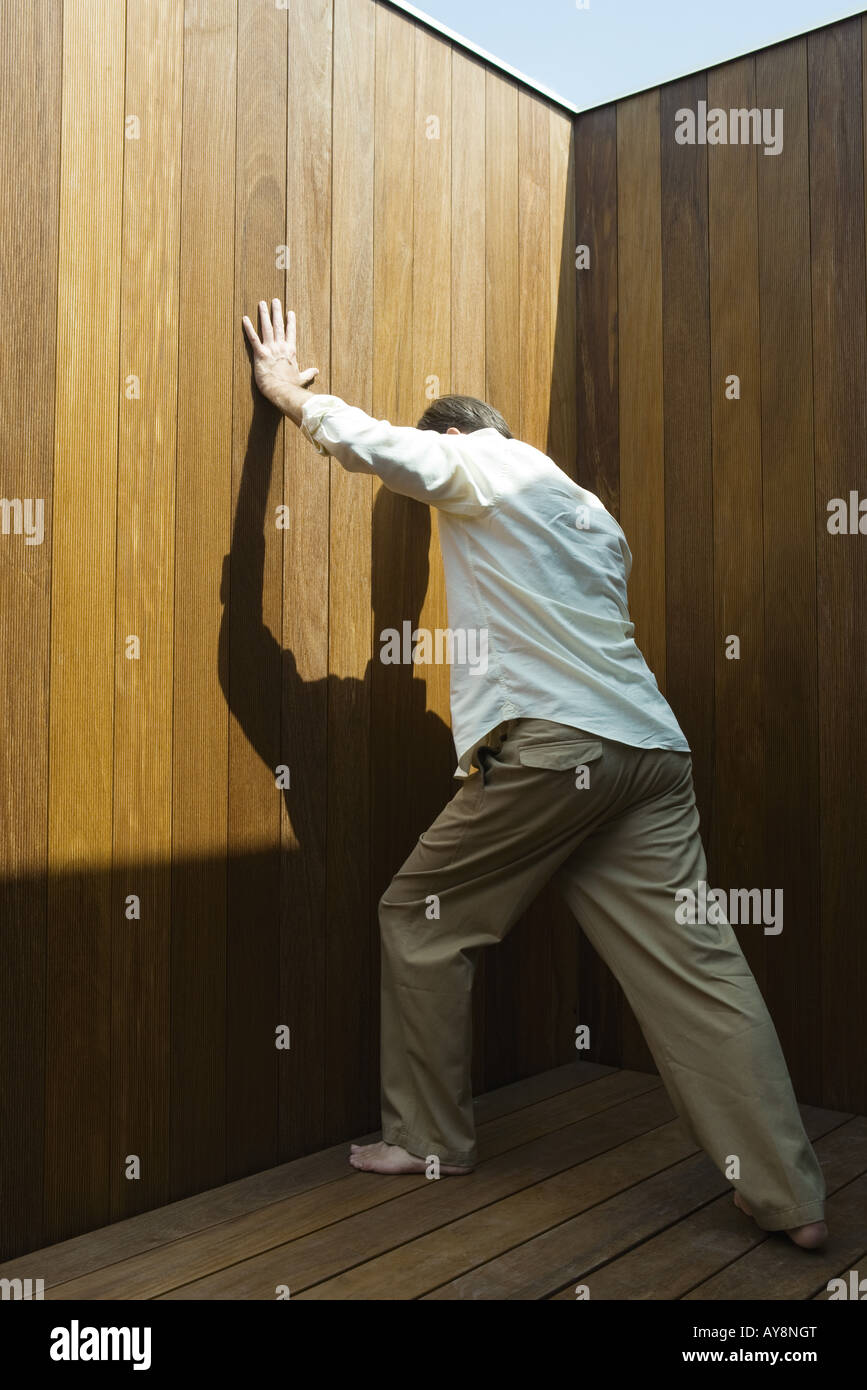 Man standing, pushing against wood paneling, side view - Stock Image