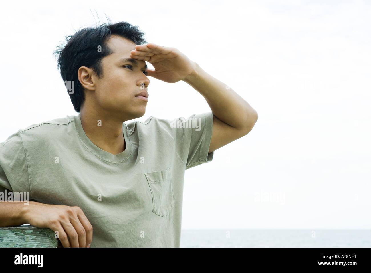 Man at the beach shading eyes, looking away, close-up - Stock Image