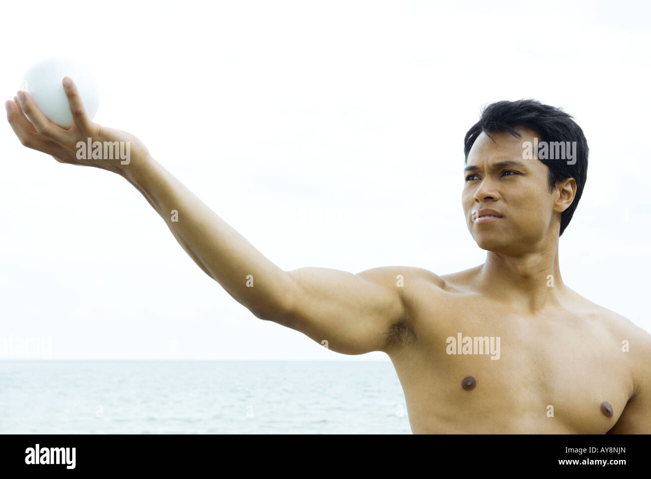 Man at the beach with arm raised, looking at ball in hand, close-up Stock Photo