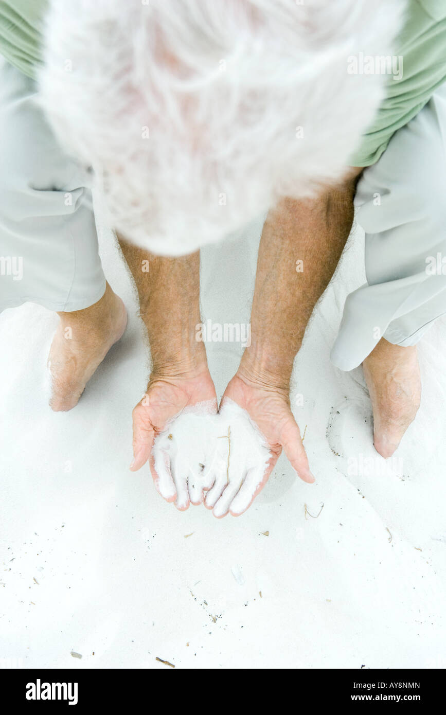 Man bending over, holding sand in both hands, high angle view - Stock Image