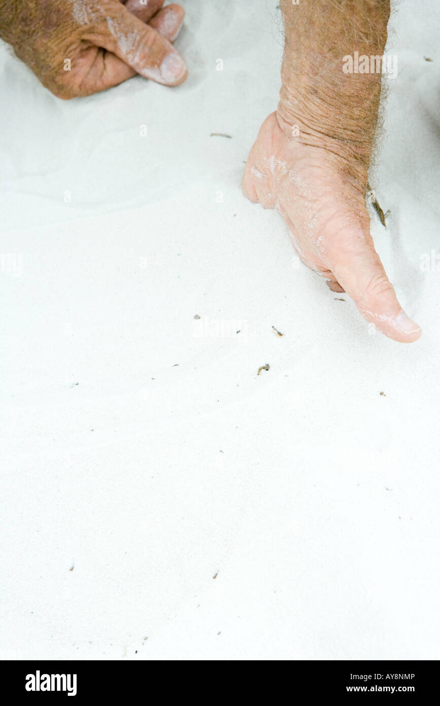 Man with hand half-buried in sand, cropped view, close-up - Stock Image