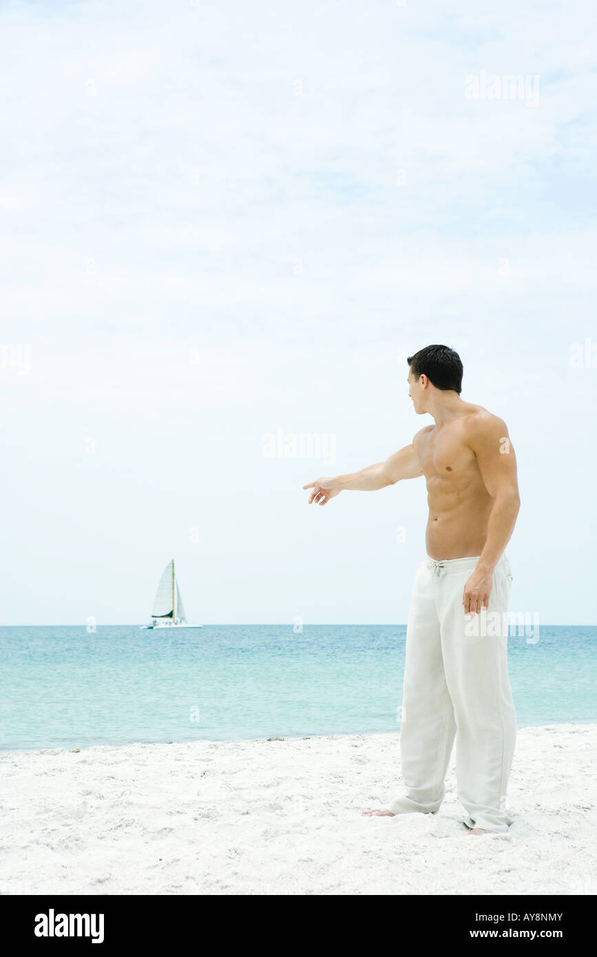 Man standing at the beach, pointing at sailboat in the distance, side view - Stock Image
