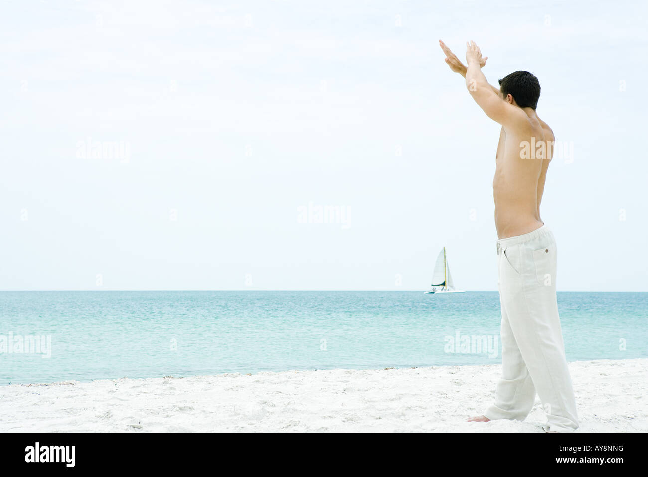 Man standing at the beach with arms raised, looking at view, side view - Stock Image