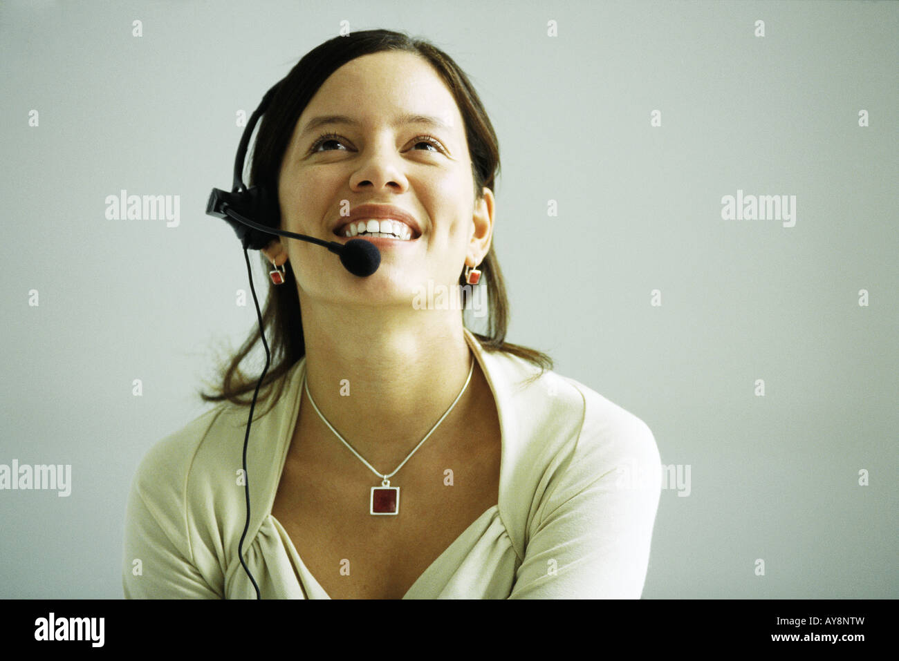 Woman wearing headset, head back, smiling, looking up - Stock Image