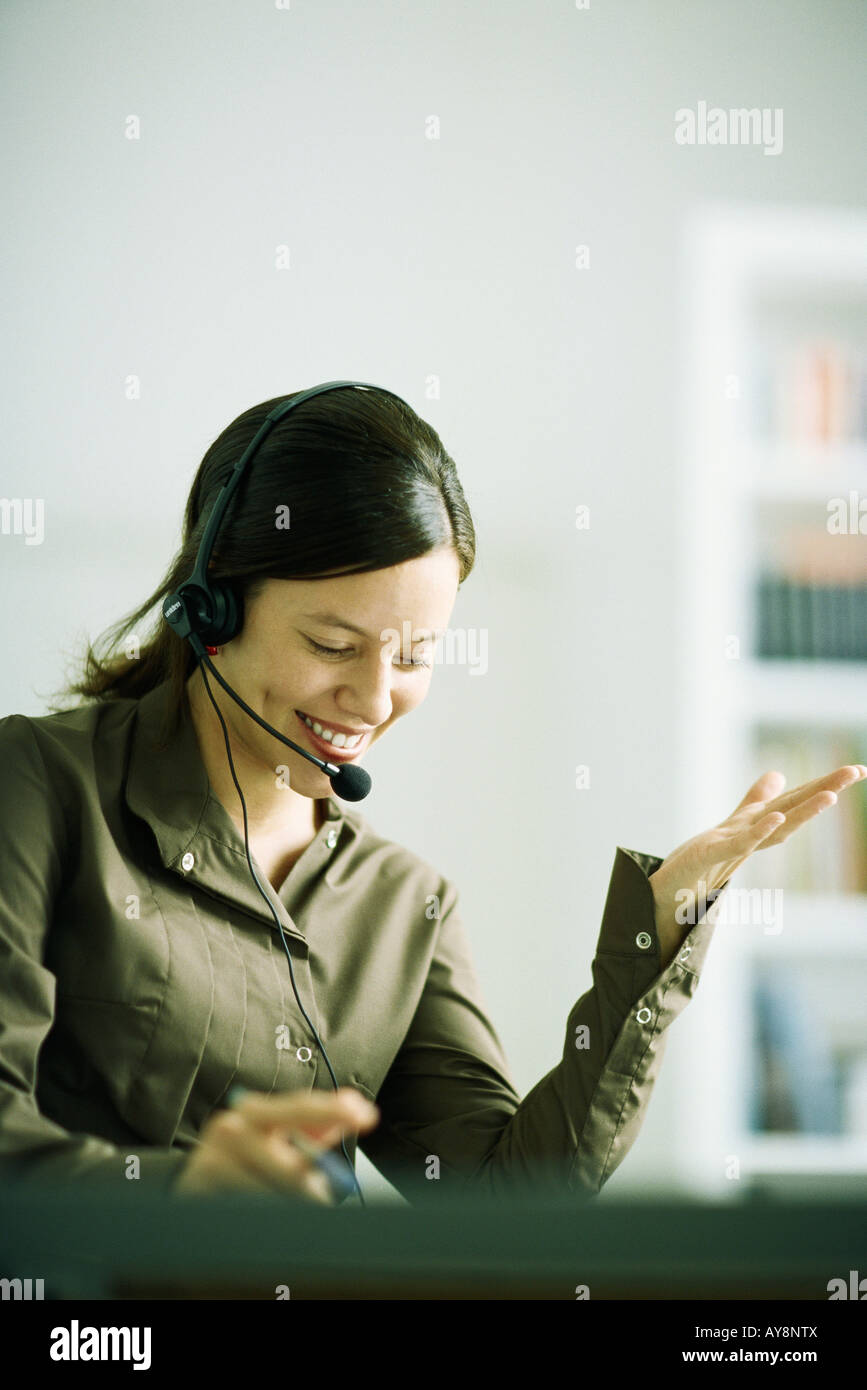 Woman wearing headset, gesturing with hand, looking down - Stock Image