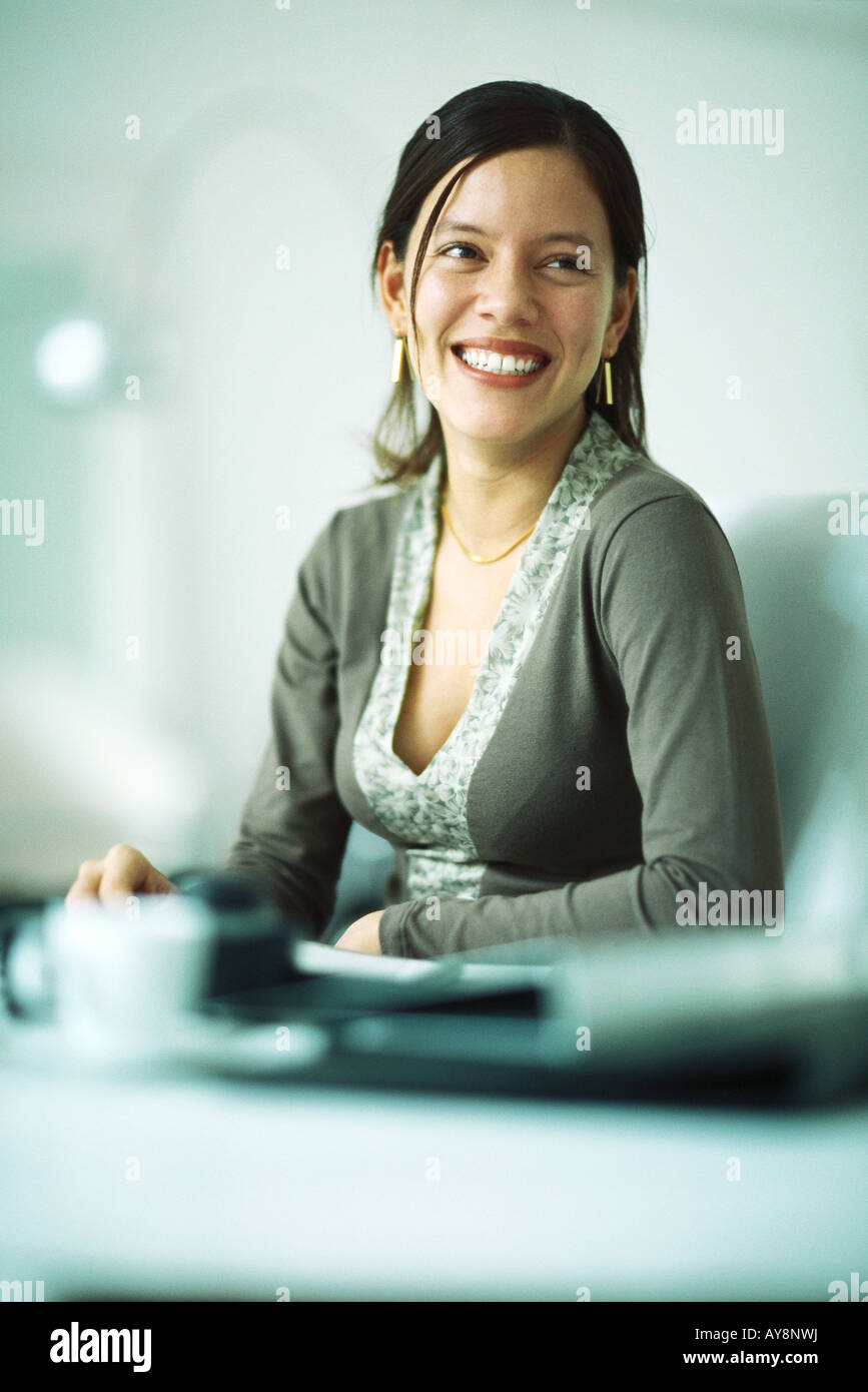 Woman sitting at desk, smiling, looking away - Stock Image