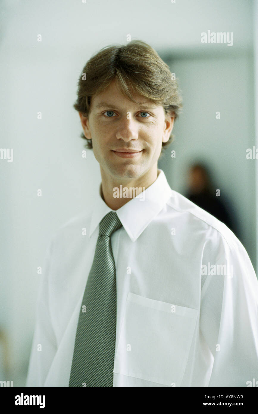 Businessman smiling at camera, portrait - Stock Image