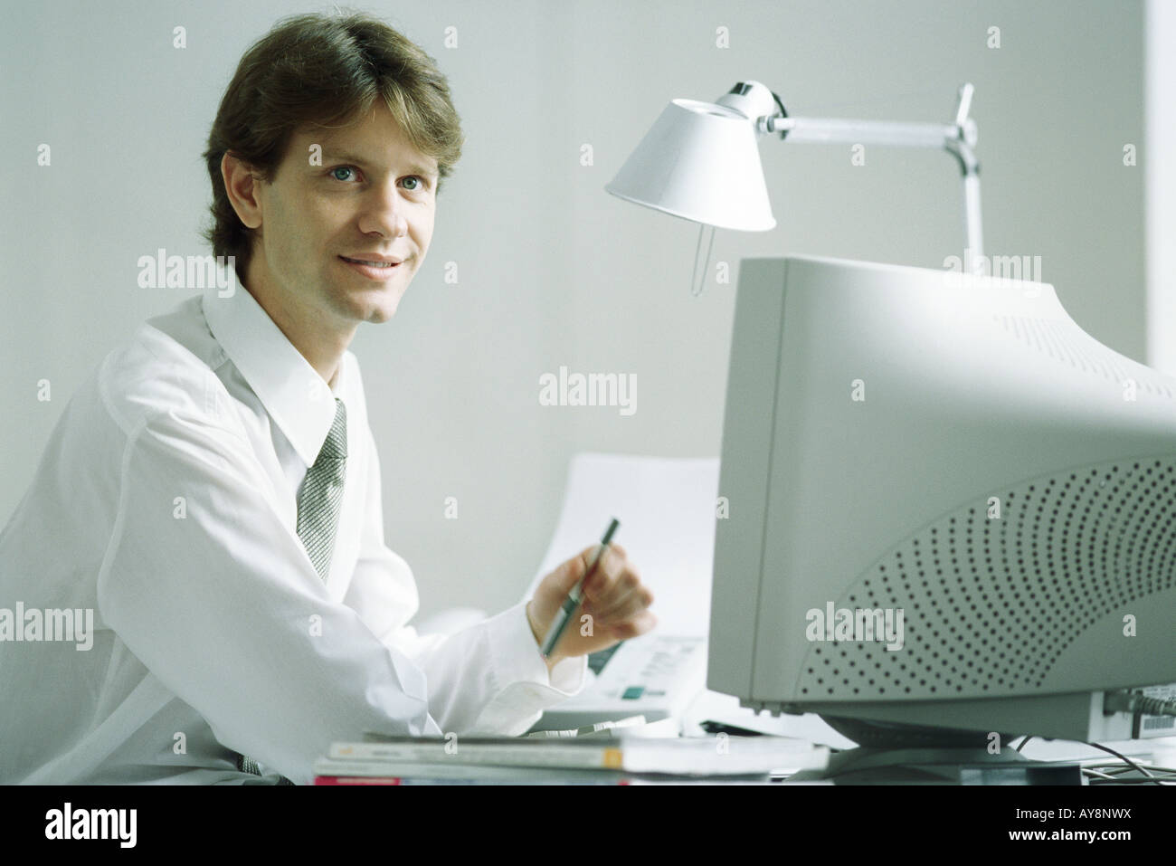 Businessman sitting at desk in front of computer, smiling, looking up - Stock Image