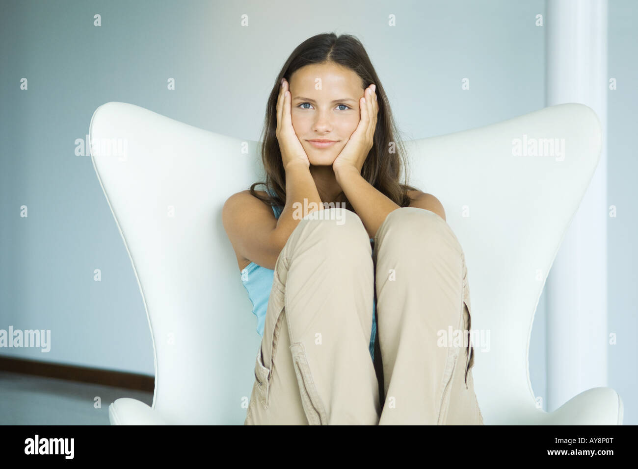 Teen girl sitting in arm chair, holding head in hands, looking at camera, three quarter length - Stock Image