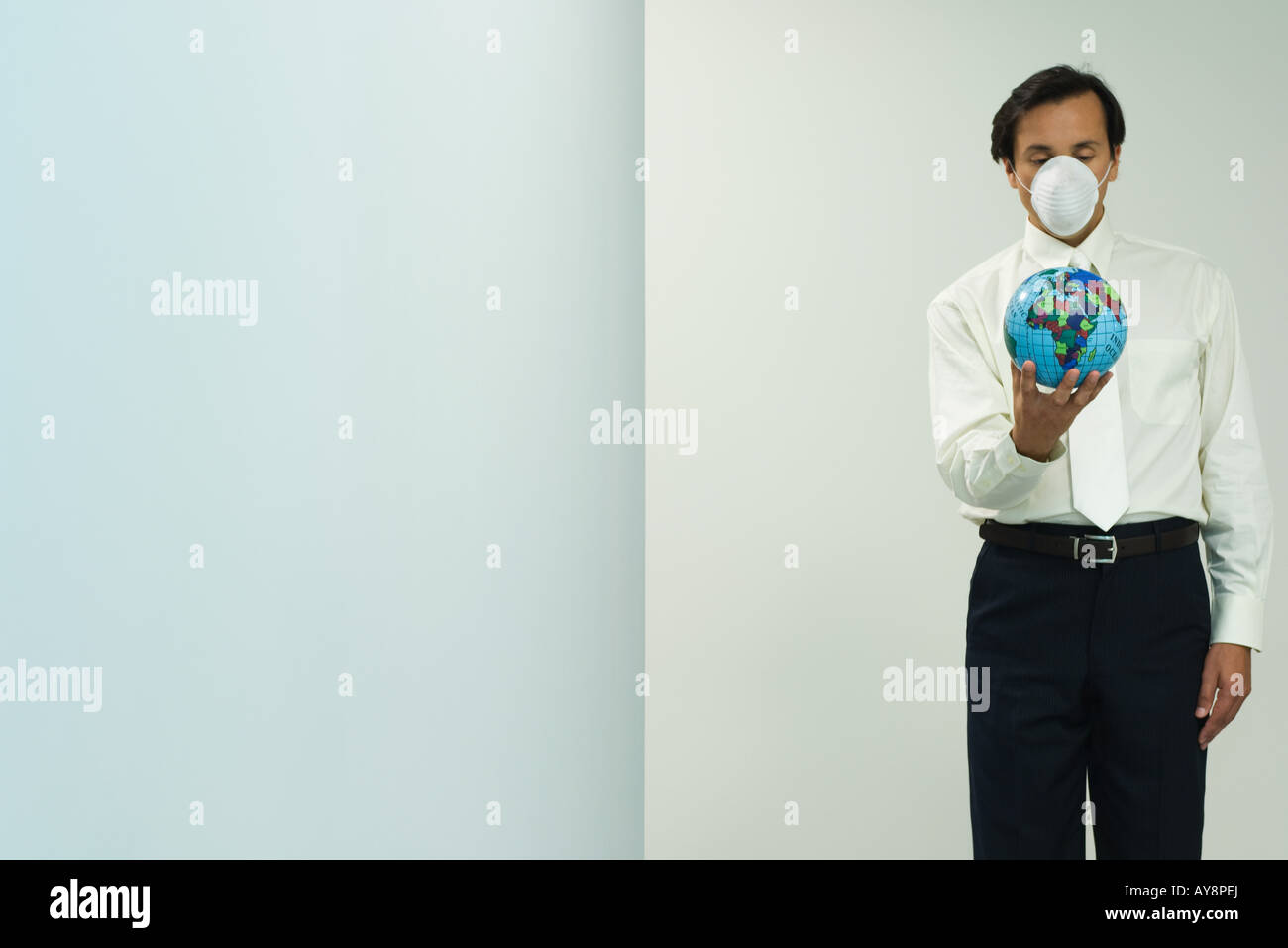 Man wearing pollution mask, holding globe, eyes closed - Stock Image