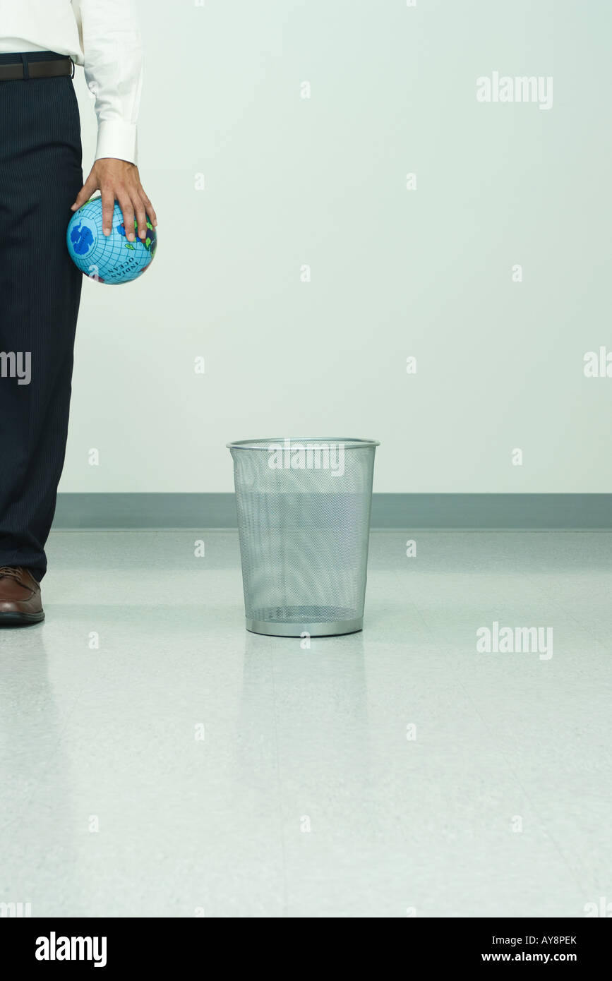 Man standing next to garbage can, holding globe in hand, cropped view Stock Photo