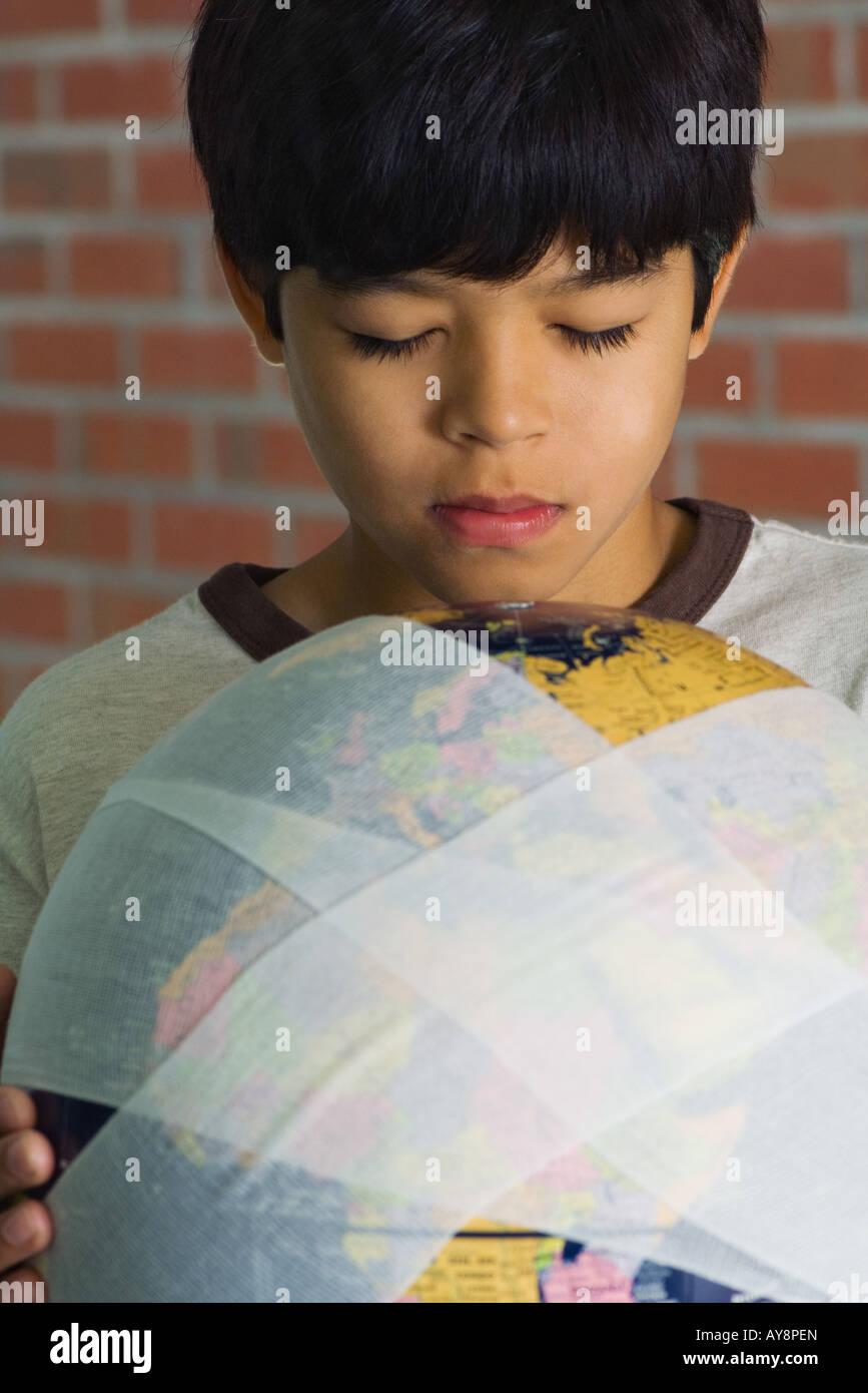 Boy holding globe wrapped in bandages, eyes closed, close-up - Stock Image
