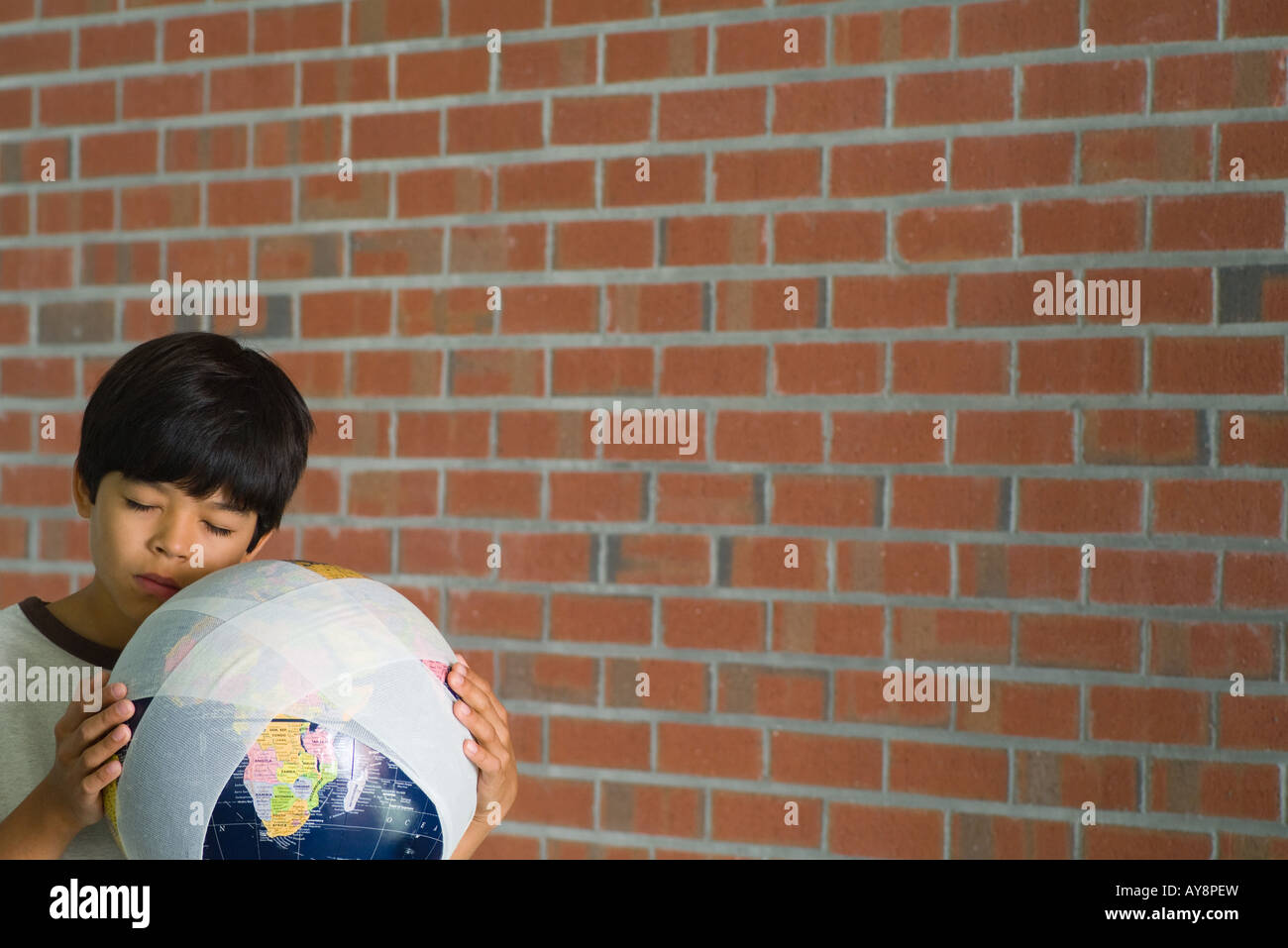 Boy holding globe wrapped in bandages against cheek, eyes closed - Stock Image