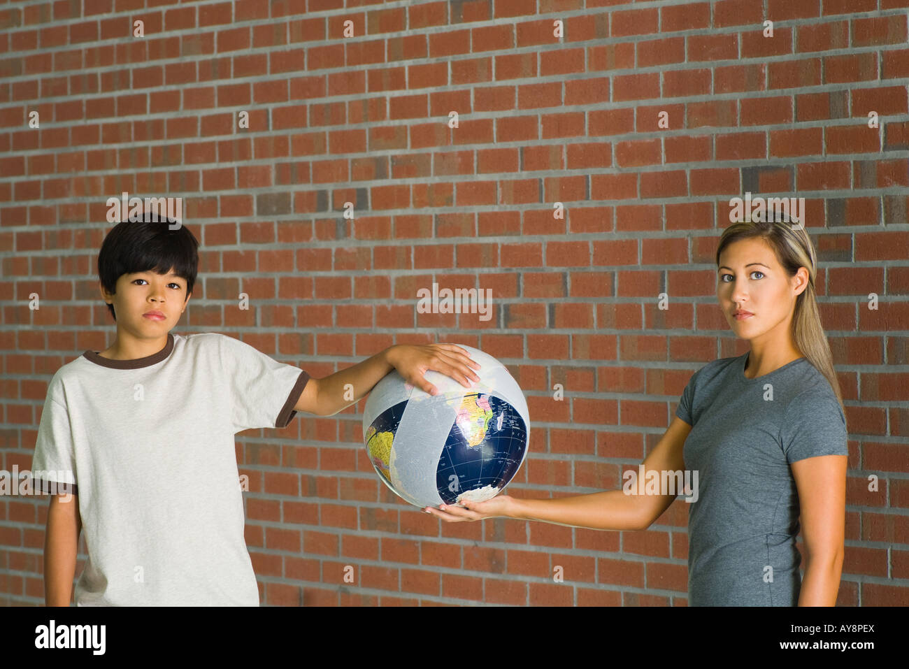 Woman and boy holding globe wrapped in bandages, both looking at camera - Stock Image