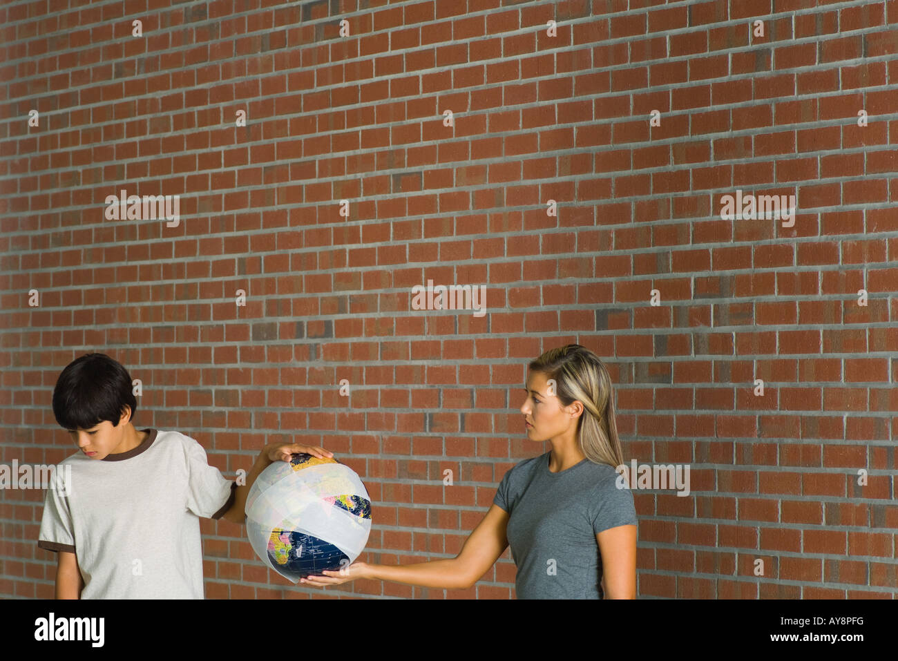 Woman and boy holding globe wrapped in bandages, woman looking at boy, boy looking down - Stock Image
