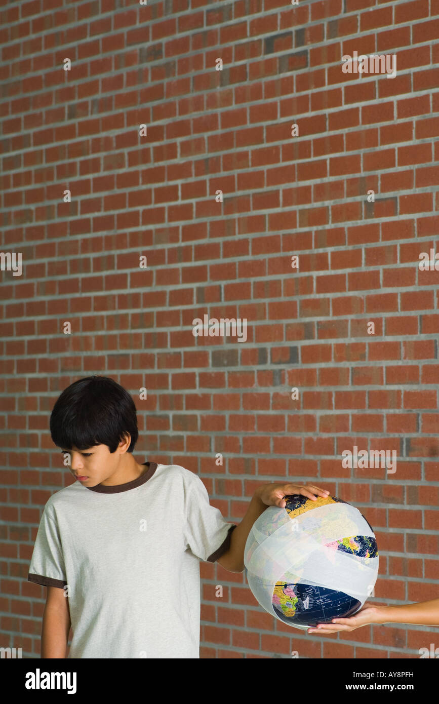 Woman handing boy globe wrapped in bandages, boy looking down, cropped view - Stock Image