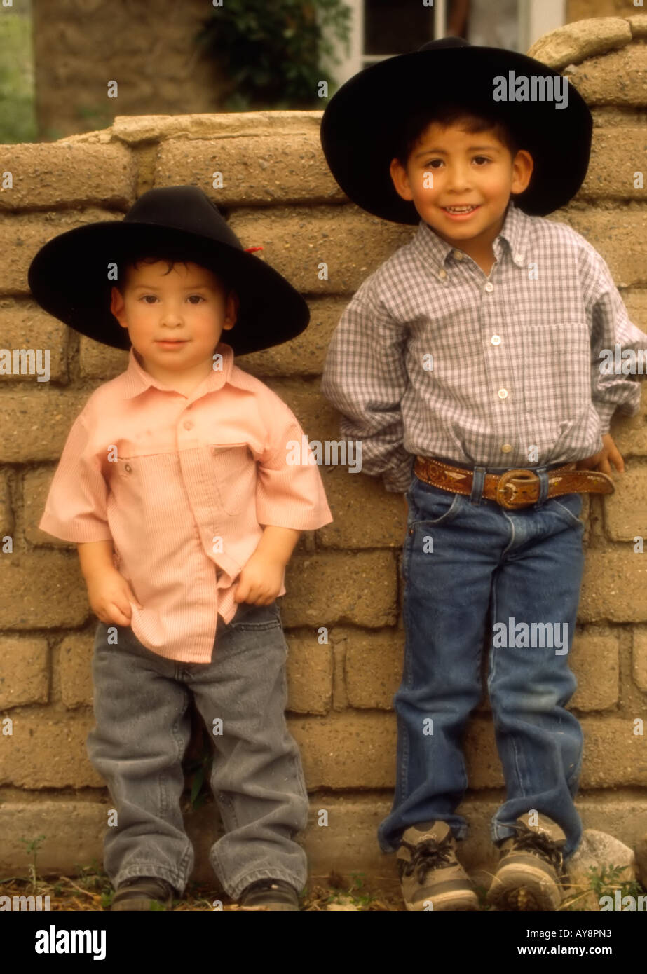 Two young hombres lean against an adobe wall, at 'Old Lincoln Days' in Lincoln, New  Mexico. - Stock Image