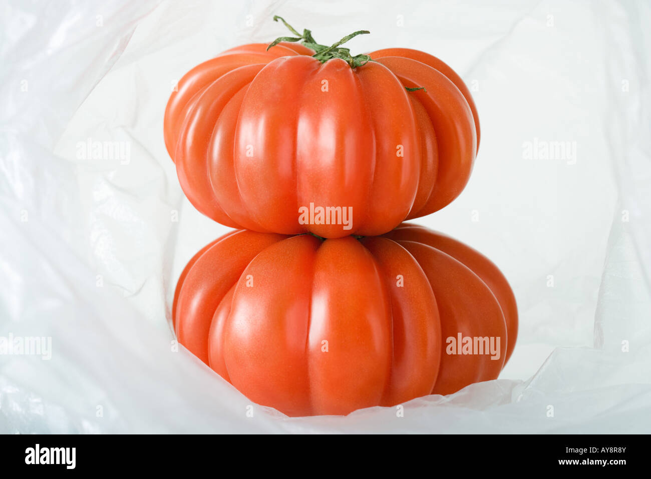 Ripe heirloom tomatoes stacked inside plastic bag, close-up - Stock Image