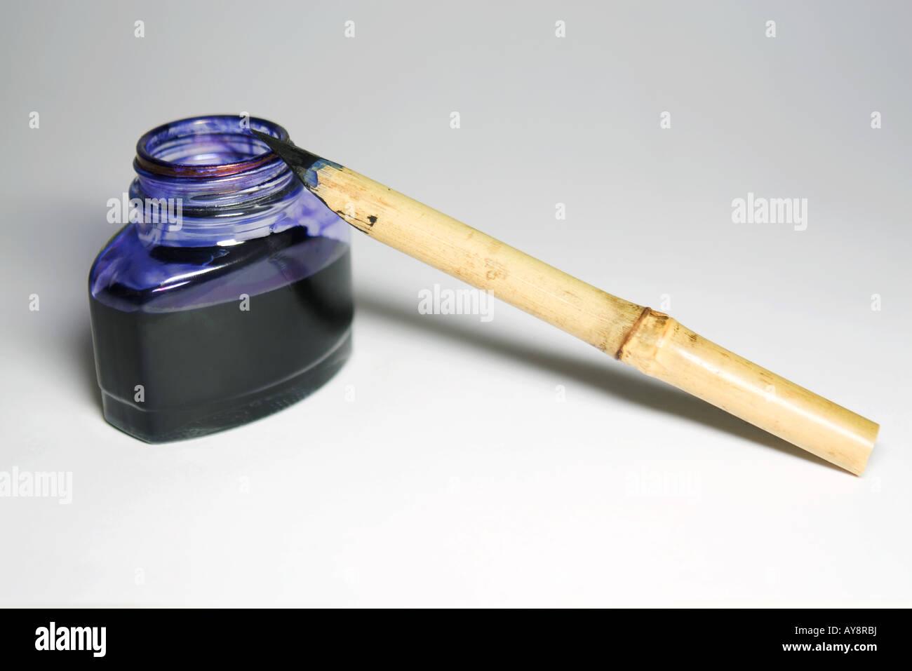 Reed pen and bottle of indigo ink, close-up Stock Photo