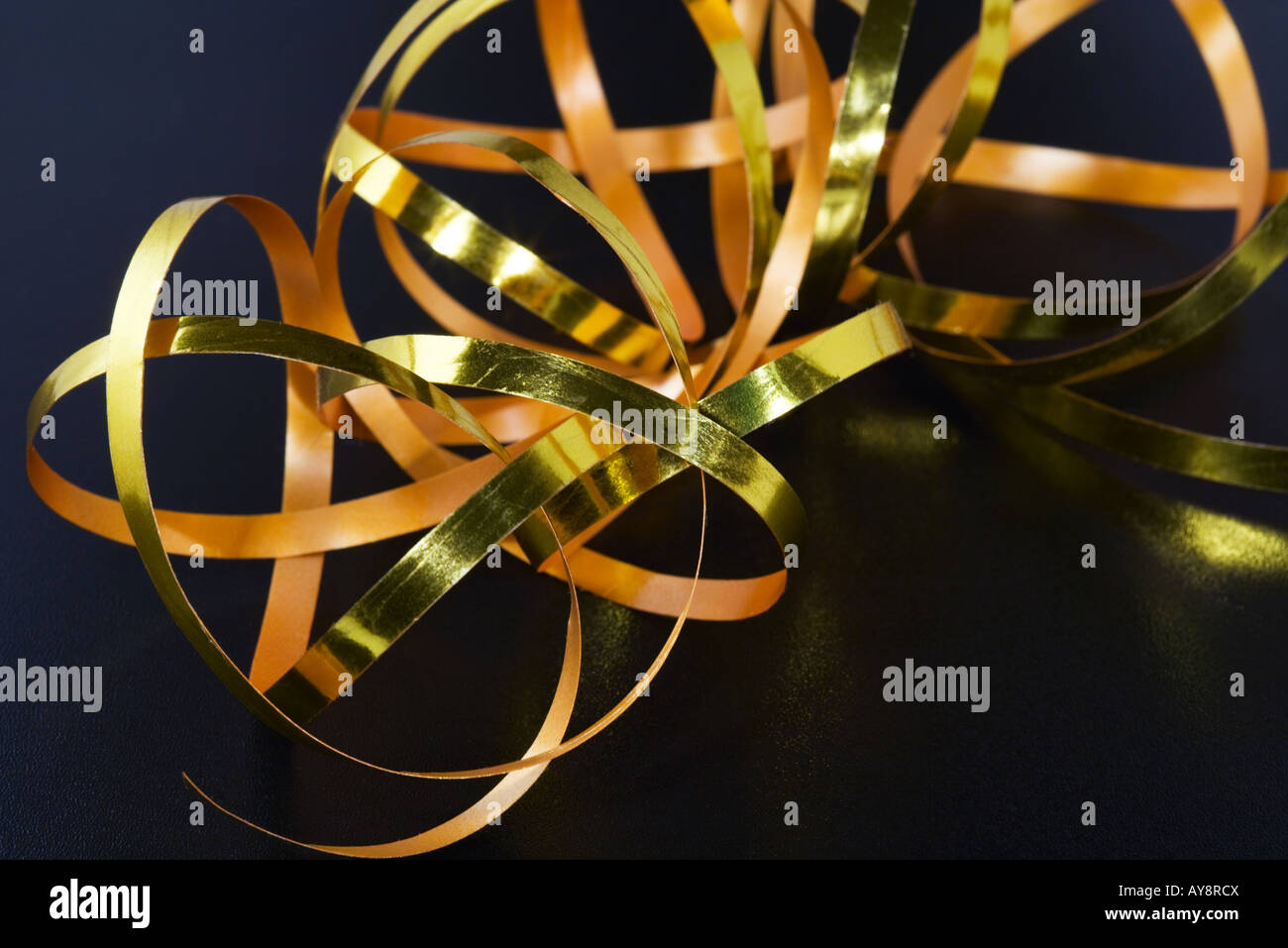 Gold-colored gift-wrap ribbon, close-up - Stock Image