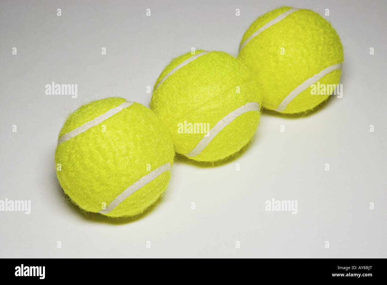 Three tennis balls in a row, close-up - Stock Image