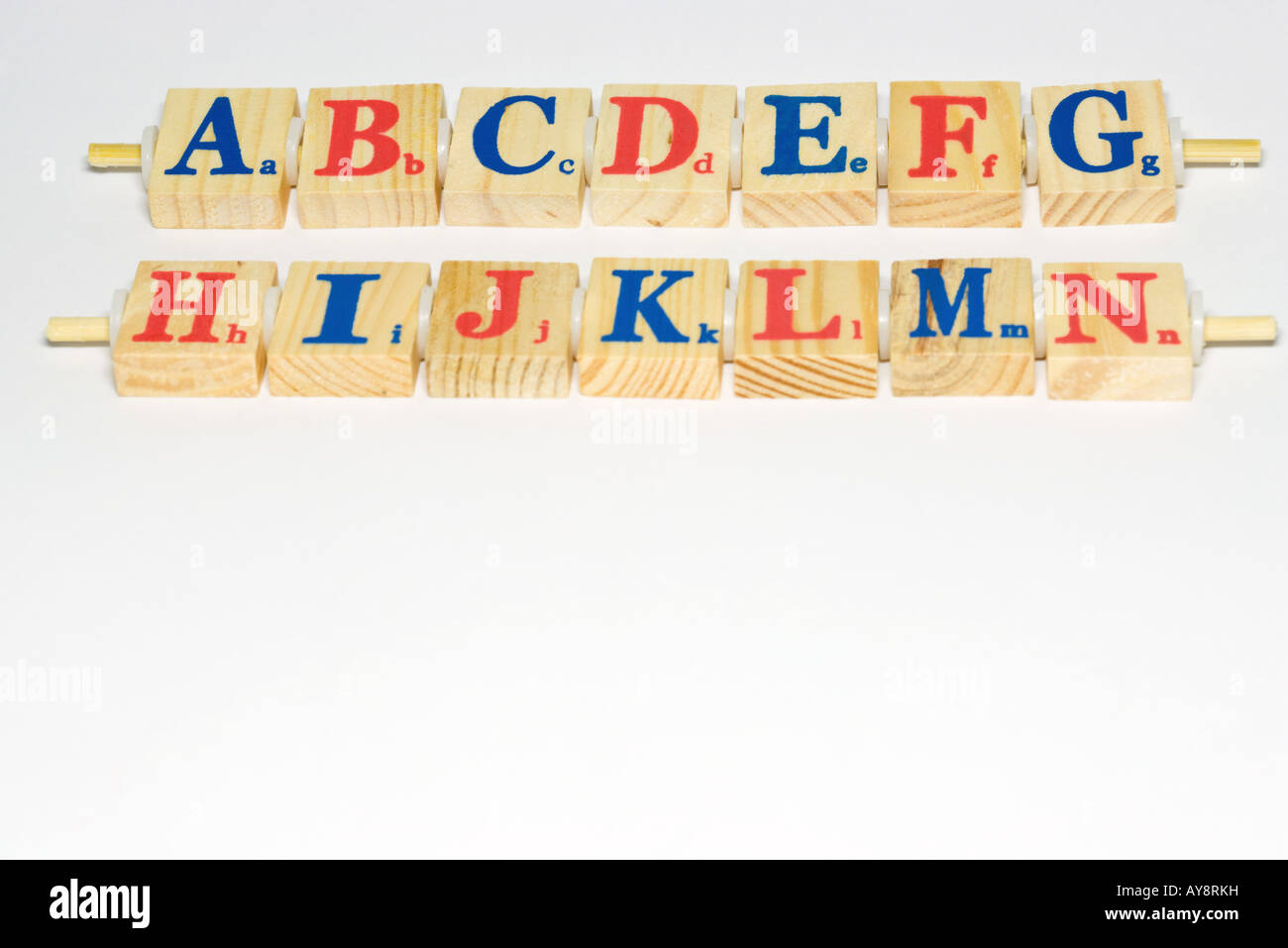 Wooden alphabet blocks lined up, close-up - Stock Image