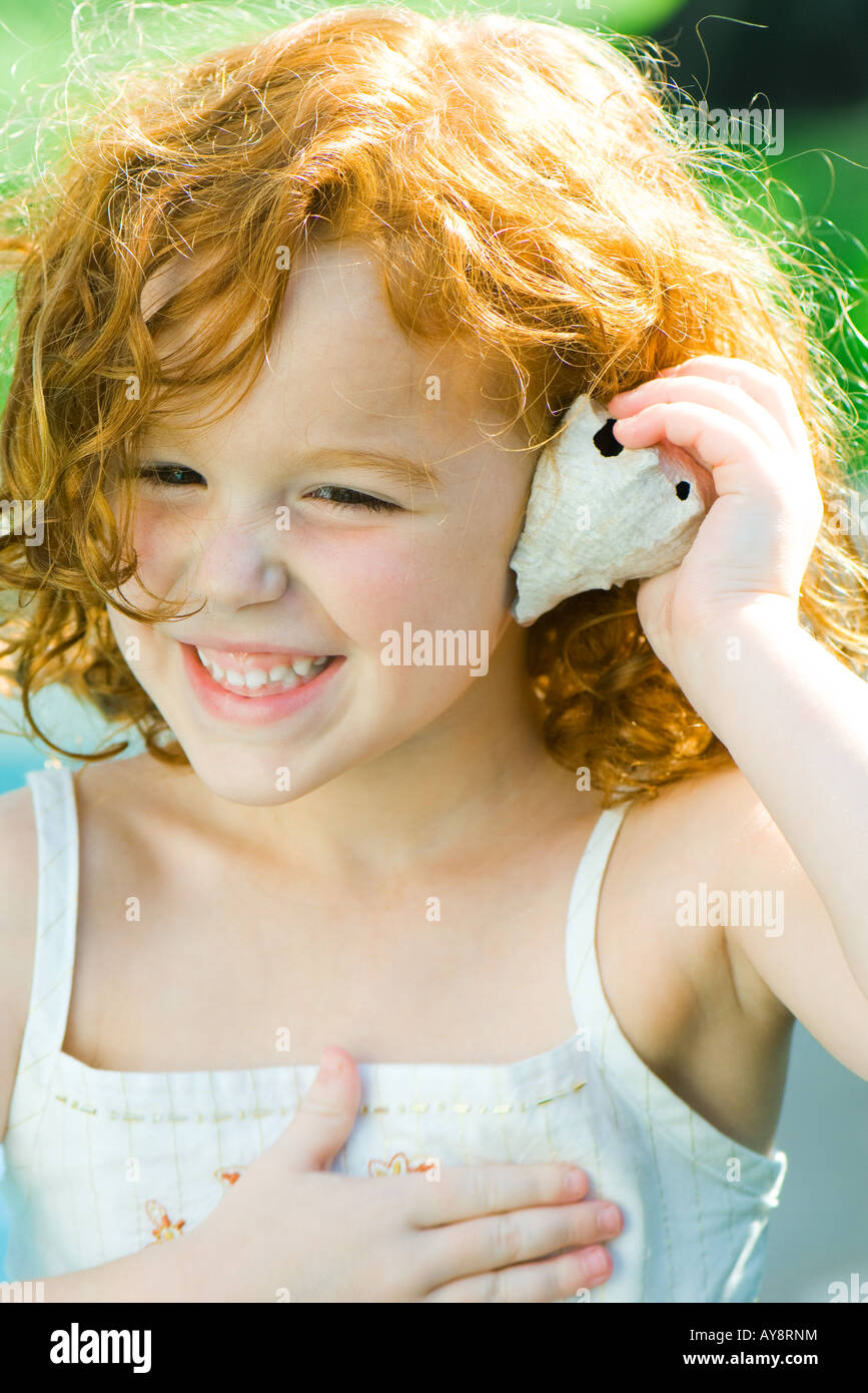 Little girl holding seashell up to ear, smiling, looking away - Stock Image