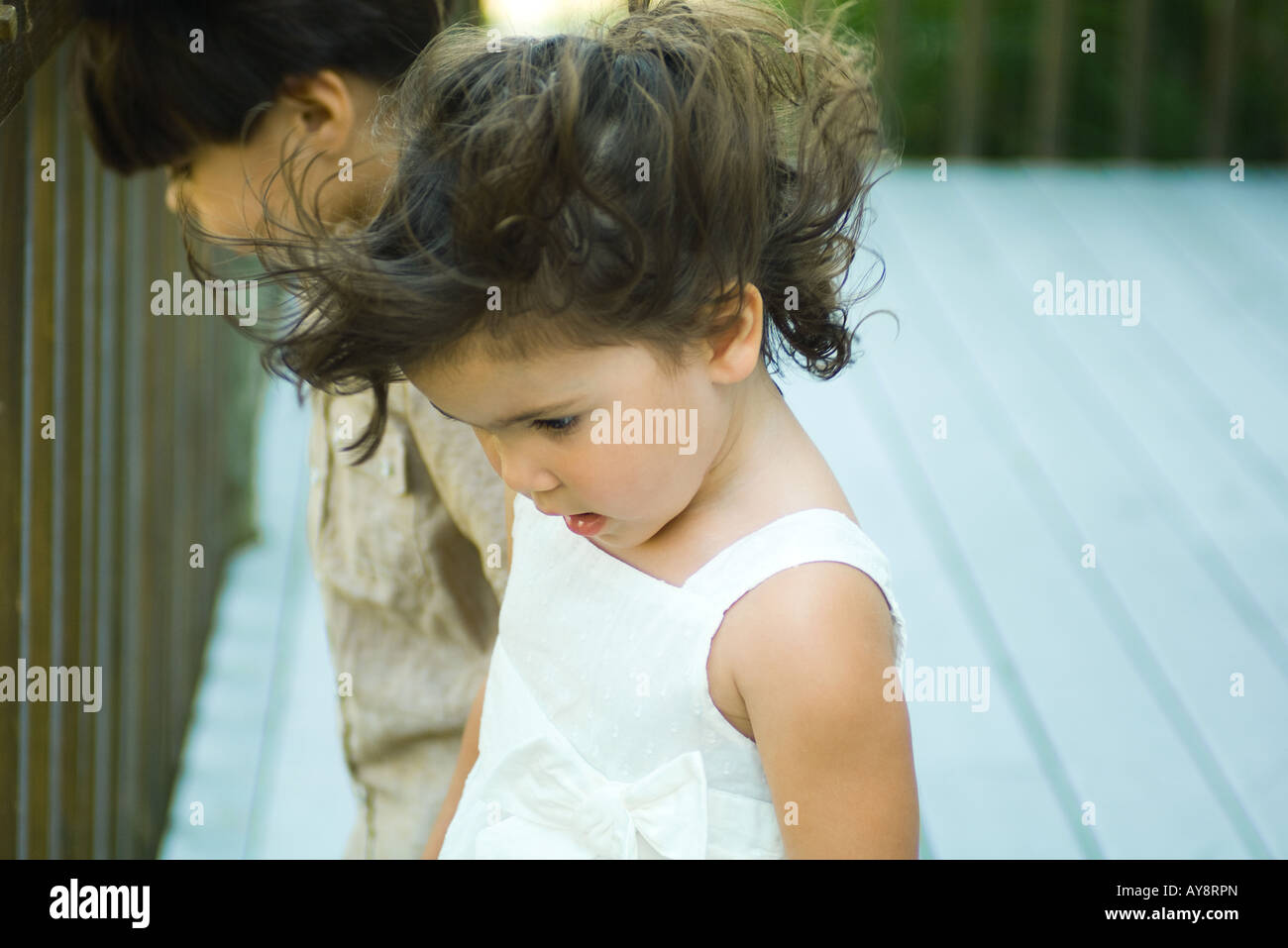 Little girl standing outdoors, looking down, hair tousled by wind, boy standing in background - Stock Image