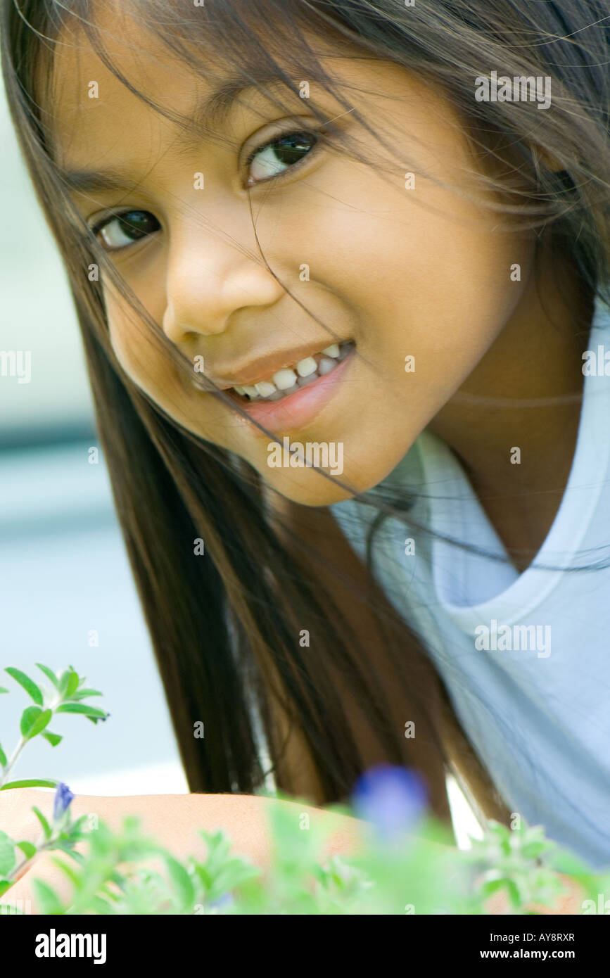 Little girl leaning over flowering plant, hair tousled by breeze, smiling at camera - Stock Image