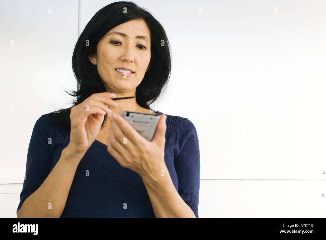 Woman using palmtop, looking down, smiling - Stock Image