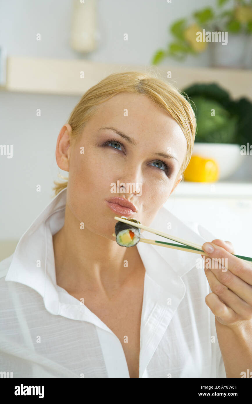 Woman holding up maki sushi with chopsticks, looking up, puckering lips - Stock Image