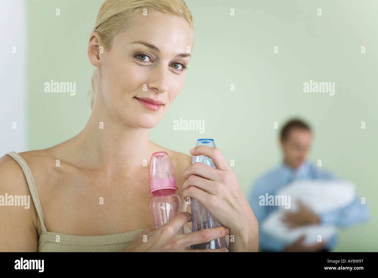 Woman holding baby bottles, smiling at camera, man holding baby in background - Stock Image