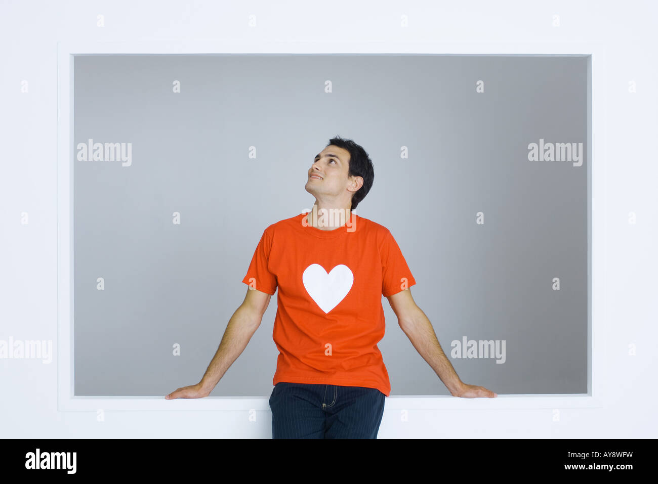 Man wearing tee-shirt with heart symbol, looking up, smiling - Stock Image