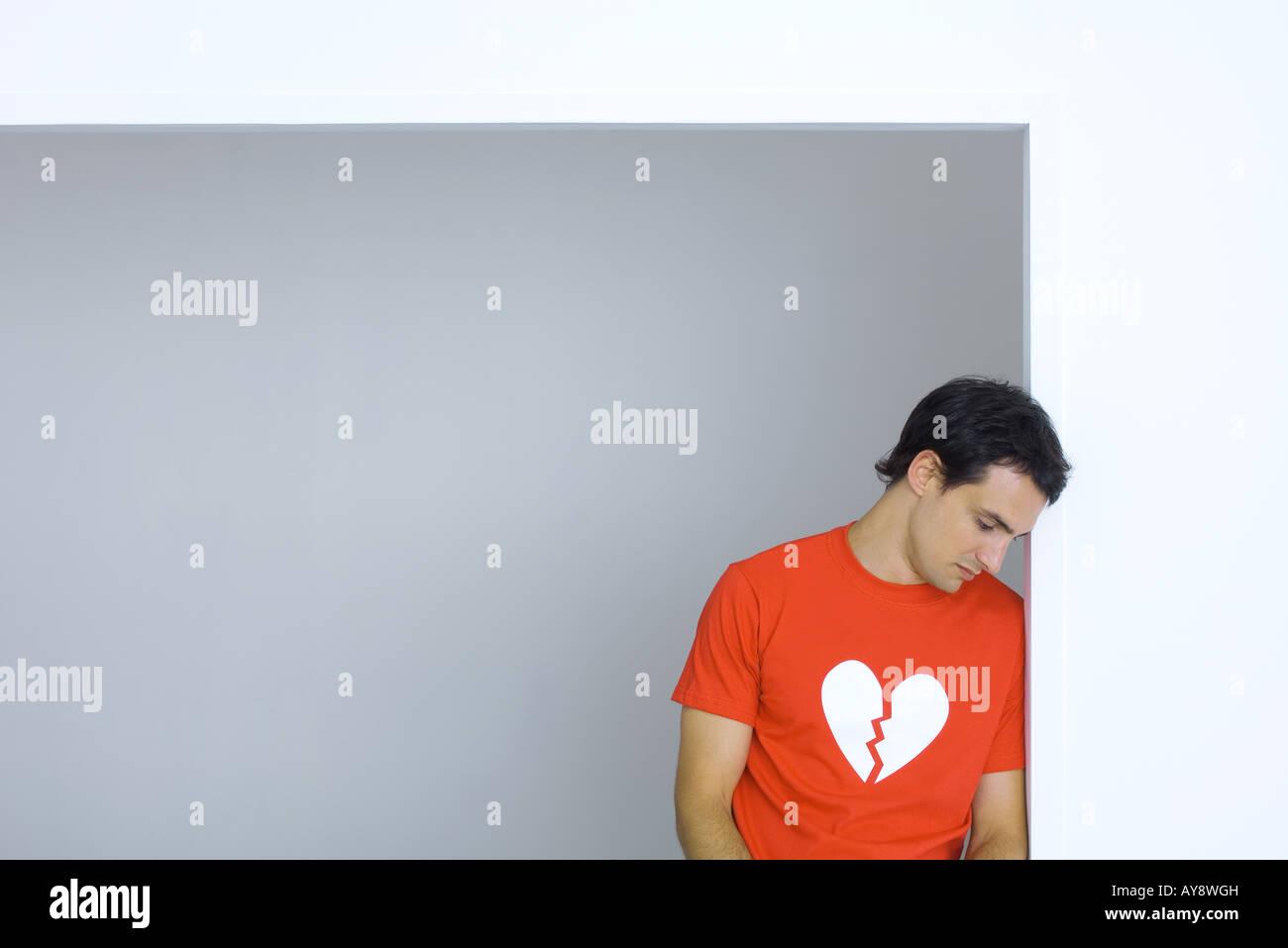 Man wearing tee-shirt with broken heart symbol, looking down - Stock Image