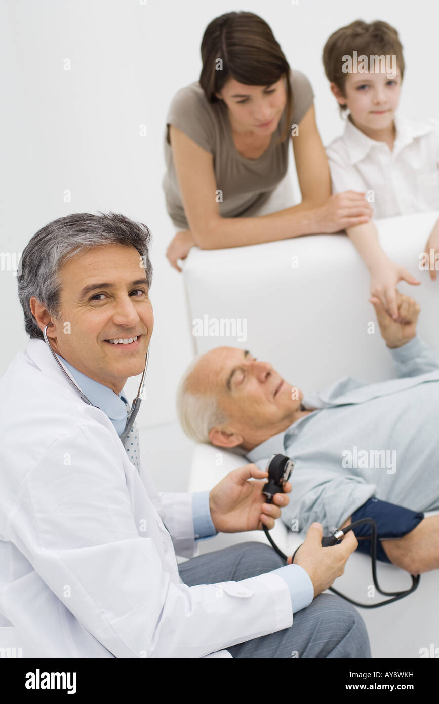 Doctor measuring patient's blood pressure, smiling over shoulder at camera, patient's family in background - Stock Image